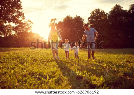 Happy young children with parents running in park