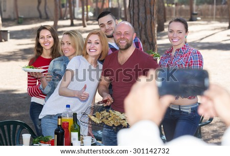 Happy young colleagues making mutual photo at summer grill party - stock photo
