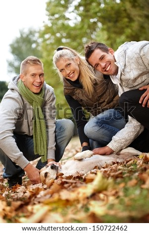 Happy young companionship stroking dog in autumn park, having fun, smiling. - stock photo