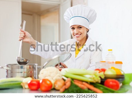 Happy young cook in white uniform  with ladle at commercial kitchen   - stock photo