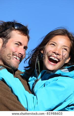 Happy young couple active outdoors. Smiling portrait of couple outside in jackets during hiking vacation. Asian woman model and Caucasian male model/ - stock photo