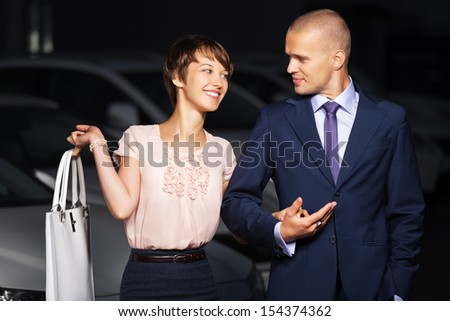 Happy young couple against a car parking - stock photo