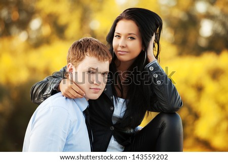 Happy young couple against an autumn nature background - stock photo