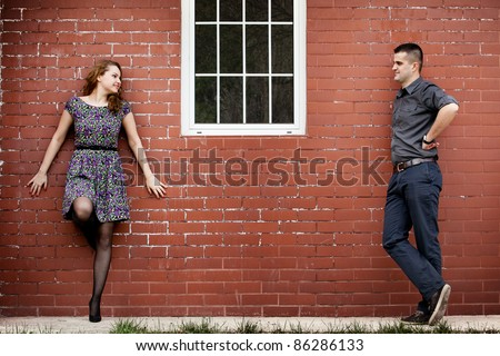 Happy young couple and house with brick wall - stock photo