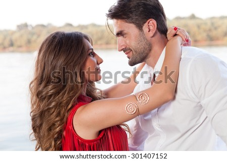 Happy young couple at the river - stock photo