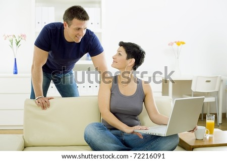 Happy young couple browsing internet on laptop computer at home, smiling.?