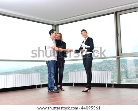 happy young couple buying new home with real estate agent and  looking big comfort bright apartment plans and taking key - stock photo