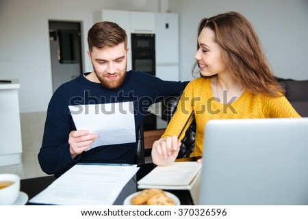 Happy young couple calculating bills at home - stock photo