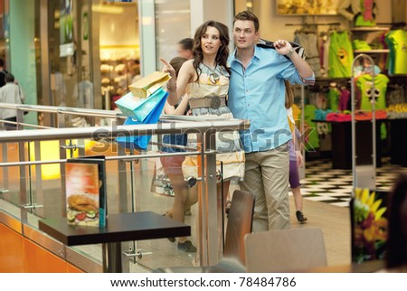 Happy young couple carrying shopping bags - stock photo