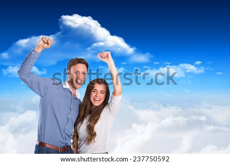 Happy young couple cheering against bright blue sky with clouds - stock photo