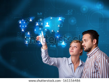 Happy young couple choosing from social network map - stock photo