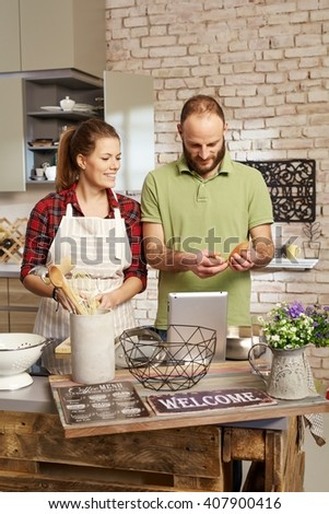 Happy young couple cooking together at home in kitchen.