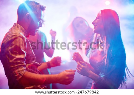 Happy young couple dancing in night club - stock photo