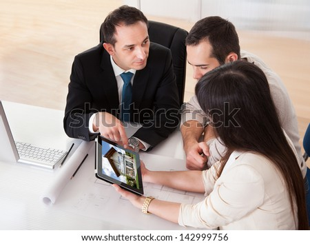 Happy Young Couple Discussing With Consultant In Office - stock photo