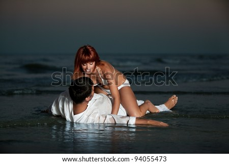 happy, young couple, dressed in white, kissing, hugging on a desert beach shore, at sunset