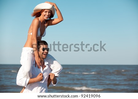 happy young couple dressed in white, on the beach, on a piggy back ride - stock photo