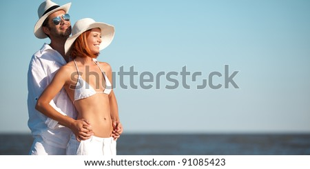 happy young couple, dressed in white, standing on a beach, smiling, holding each other - stock photo