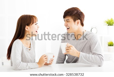 happy young Couple drinking coffee  In living room - stock photo