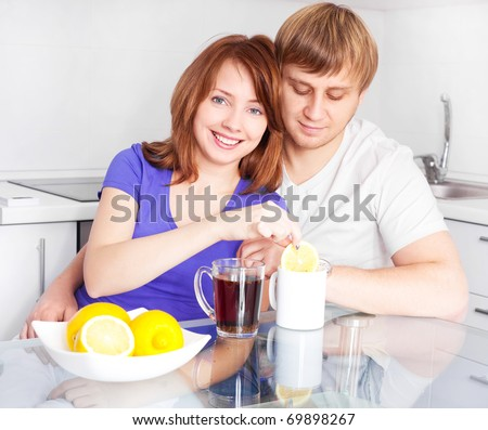 happy young couple drinking tea with lemon in the kitchen at home