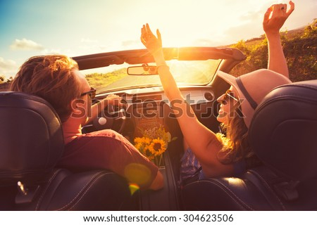 Happy Young Couple Driving Along Country Road in Convertible at Sunset. Freedom Adventure Road Trip - stock photo
