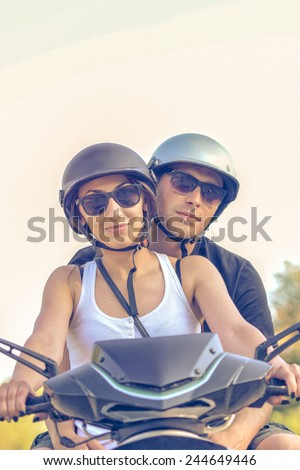 Happy young couple driving scooter  - stock photo
