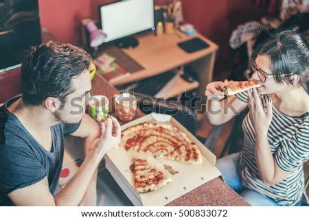 Happy young couple eating pizza, drinking coffee at the kitchen