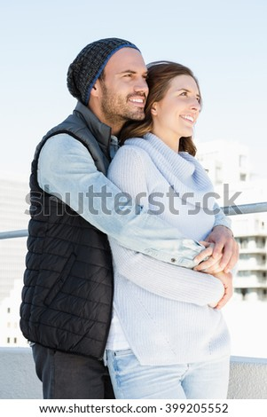 Happy young couple embracing and smiling outdoors - stock photo