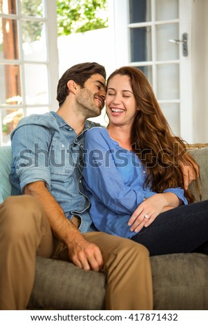 Happy young couple embracing each other in living room
