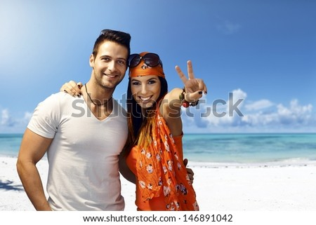 Happy young couple embracing on the beach, smiling, showing victory sign. - stock photo
