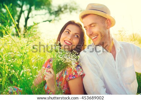 Happy Young Couple enjoying nature outdoors. Beautiful Girlfriend with her boyfriend sitting on summer field with bunch of wildflowers and smiling. Joyful people, vacation concept