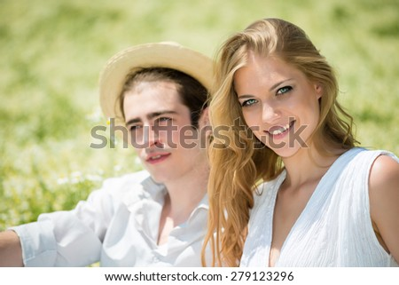 Happy, young couple enjoying on sunlight outdoors at chamomile field - stock photo