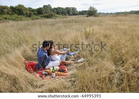 happy young couple enjoying  picnic on the countryside in the field  and have good time - stock photo