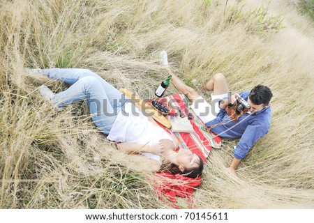 happy young couple enjoying  picnic on the countryside in the field  and have good time