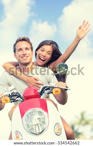 Happy young couple enjoying scooter ride against sky. Cheerful woman with arm raised screaming while man driving vehicle. Carefree male and female are enjoying their summer vacation. - stock photo