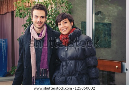 Happy young couple entering in hotel lobby. - stock photo