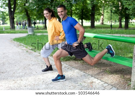 Happy young couple exercising outdoors, using a park bench to do a leg exercise - stock photo