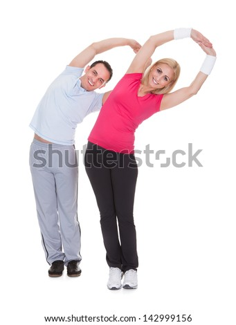 Happy Young Couple Exercising Over White Background - stock photo