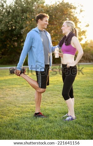 Happy young couple exercising together in a park - stock photo
