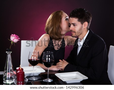 Happy young couple flirting at restaurant table - stock photo