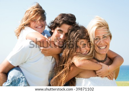 Happy young couple giving two children piggyback rides smiling at camera - stock photo