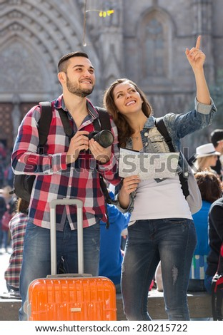 Happy young couple going sightseeing with camera through square of European city - stock photo