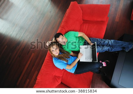 happy young couple have fun and relax at comfort bright apartment and work on laptop computerhappy young couple have fun and relax at comfort bright apartment and work on laptop computer - stock photo