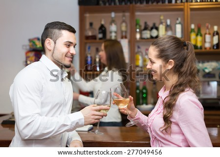 Happy young couple having a date with wine at bar. Focus on guy