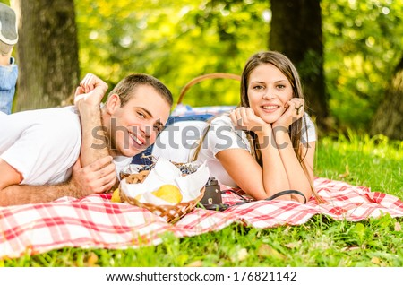 Happy young couple having a picnic and laying on the picnic cloth enjoying the autumn nature in the park - stock photo