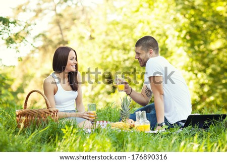 Happy young couple having a picnic in park - stock photo