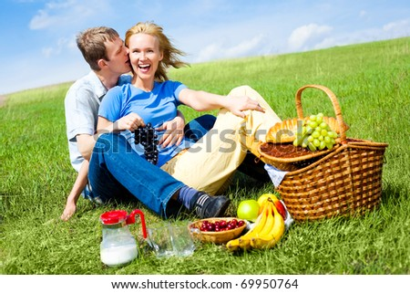 happy young couple having a picnic outdoor on a summer day - stock photo