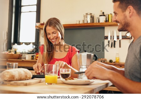 Happy young couple having breakfast together at home. Young woman and man smiling while eating breakfast in kitchen. Couple having good time during breakfast in kitchen. - stock photo
