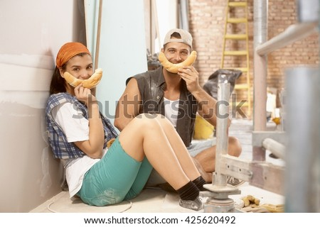 Happy young couple having fun at home renovation, preparing smiliy face from crescent roll,