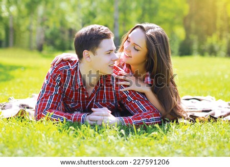 Happy young couple having fun in the park on the grass smiling in summer sunny day - stock photo