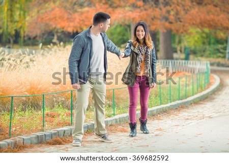 Happy young couple having fun walking through the park  - stock photo